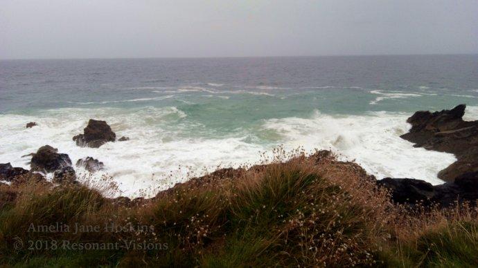 Waves meet rocks below coast path