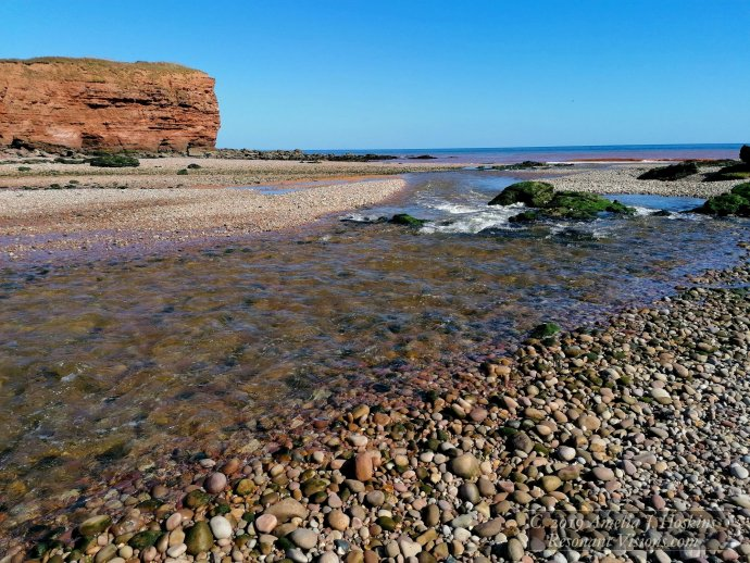 River exit to sea ripples over beach stones