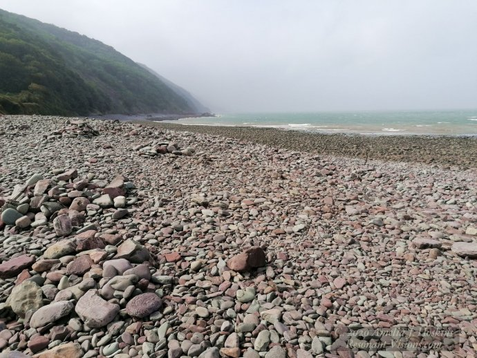Large drift of beach stones to forested headland