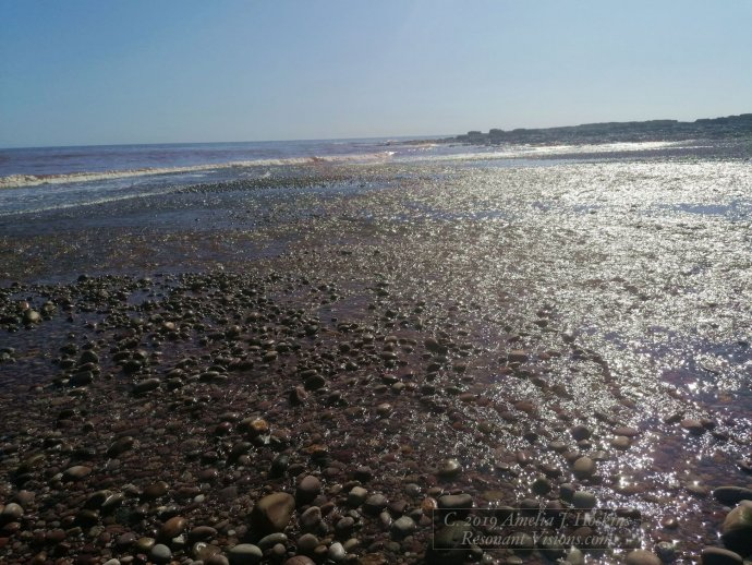 River water spreads out over pebble beach to sea